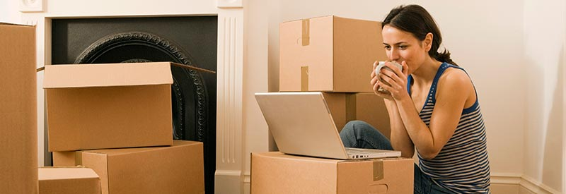 woman drinking coffee while unpacking boxes
