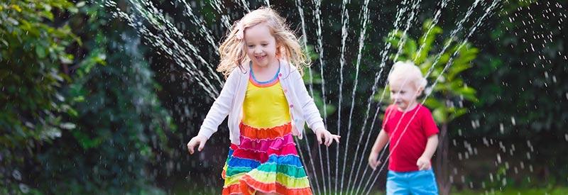 kids running through a lawn sprinkler