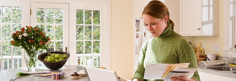 woman in kitchen reviewing her financial statements